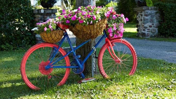decoration de jardin a faire soi meme, gazon vert, vélo en bleu et rouge, support de fleurs diy