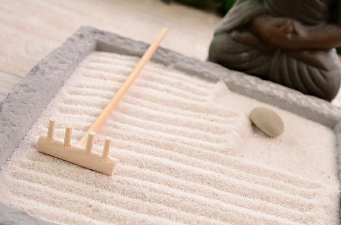 déco de jardin zen, ratisser le terrain sablé, installer des pierres, statue bouddha