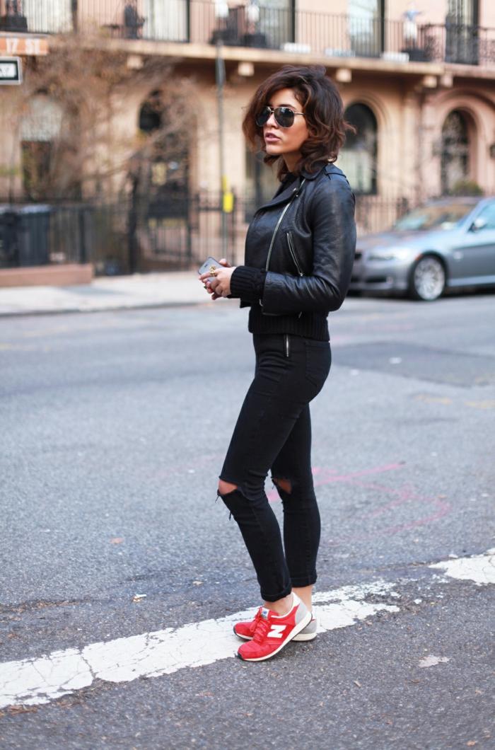 jean troué noir, baskets rouge, veste en cuir noir, lunettes de soleil noires