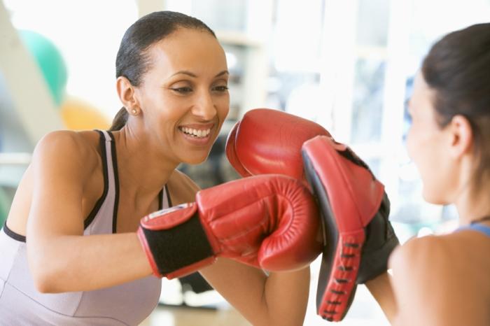 entrainement sportif, boxe femme, gants de boxe rouge, tenue sportive en rose poudré, salle de boxe