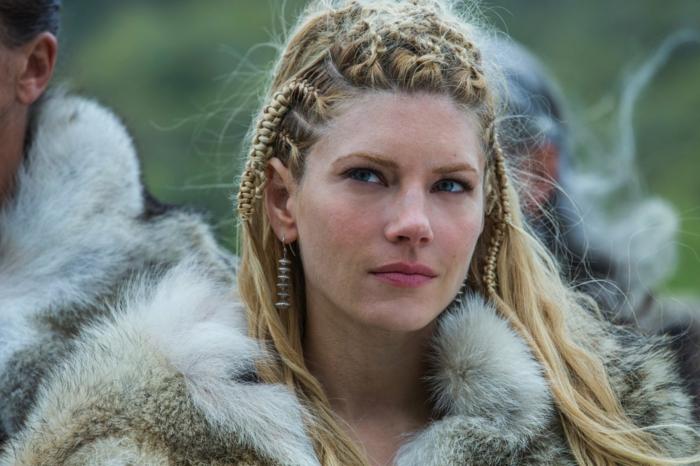 vikings lagertha, lèvres rose, manteau en simili fur, cheveux blonds tressés, boucles d'oreille en métal argenté