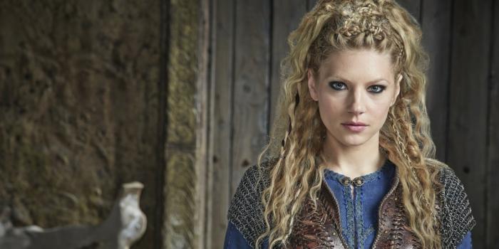 vikings lagertha, chemise bleue, lèvres rose, coiffure mi-détachée, cheveux bouclés, tresses