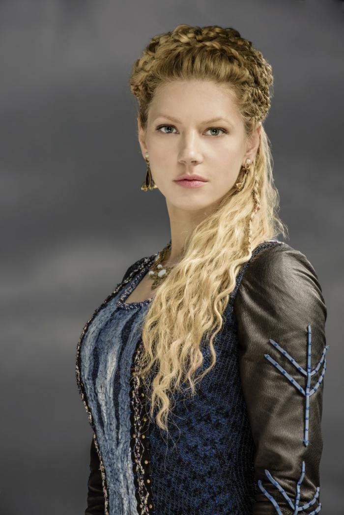 vikings lagertha, robe bleue, manches en cuir noir, maquillage naturel, boucles d'oreille en or, cheveux bouclés en nattes