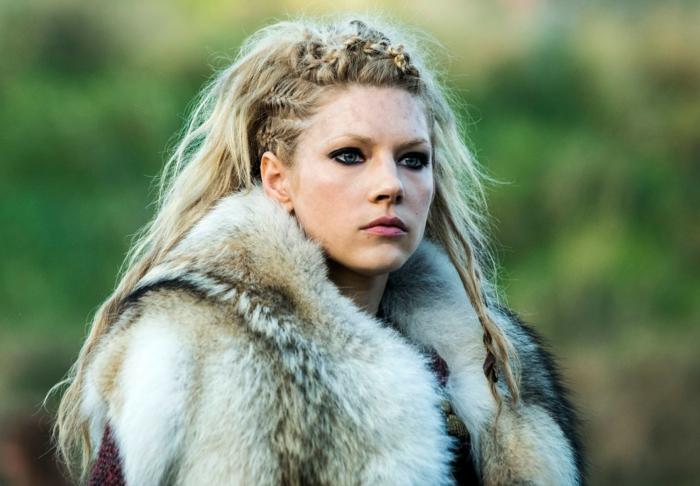 vikings lagertha, manteau en fur, yeux bleus, lèvres rose, cheveux blonds, tresses sur les côtés