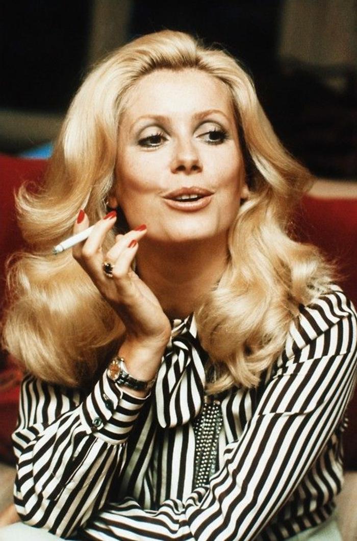 look années 60, coiffure bouclée de Catherine Deneuve habillée en une chemise rayée
