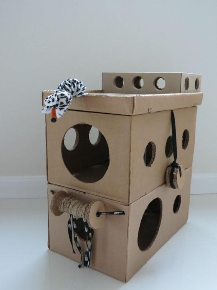 maisonnette chat, construction pour chat en carton avec des jouets de chat accrochés