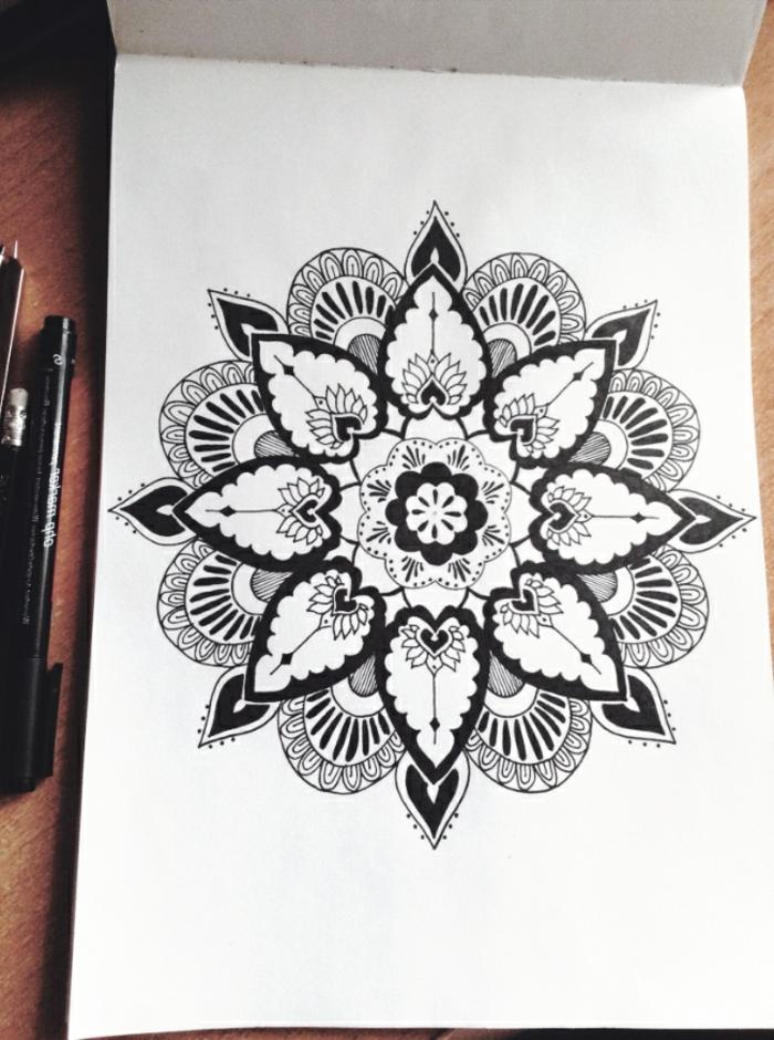 mandala facile a faire, dessin blanc et noir, crayons, agenda, table en bois, mandala à motifs floraux