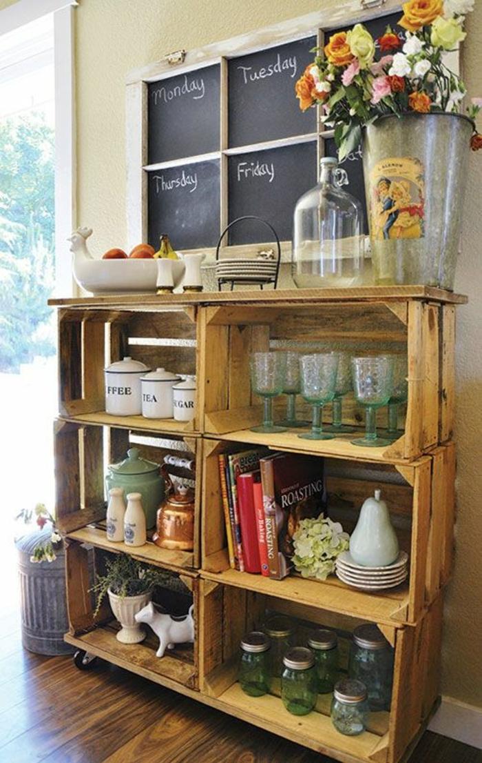 meuble de rangement en caisses en bois à roulettes, vaisselier, pots en verre, verres à vin, décorations, seau, bouquet de fleurs, tableau horraires