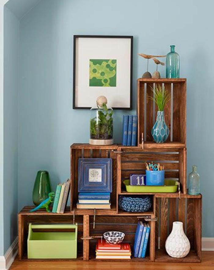 meuble en cagette asymetrique, livres, accessoires décoraifs, plantes, pot a crayon, vases, deco murale, mur couleur bleue