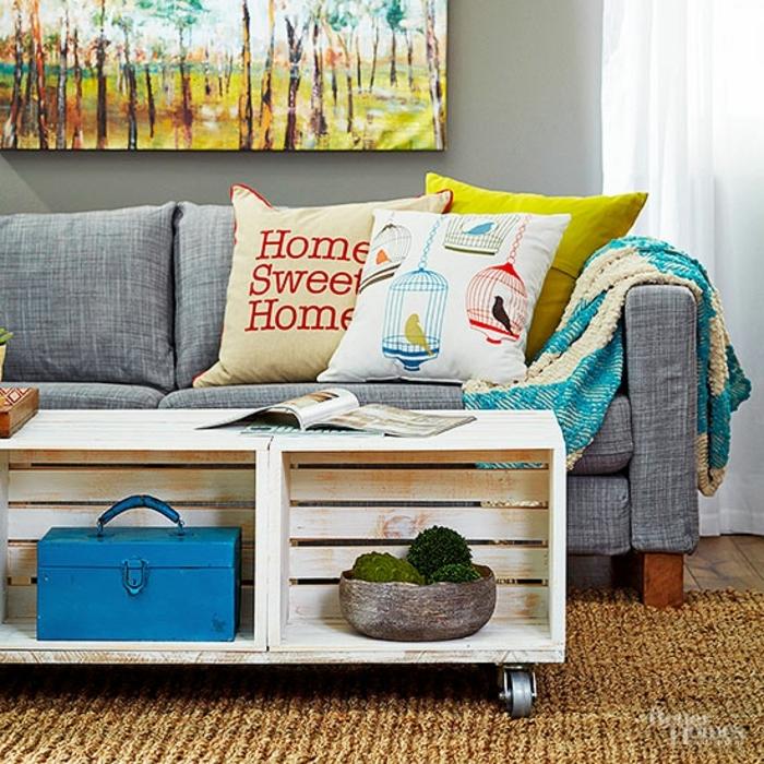 canapé gris, table basse de cagette en bois à roulettes, tapis amrron, coussins multicolores, deco murale astistique, accessoires deco vintage