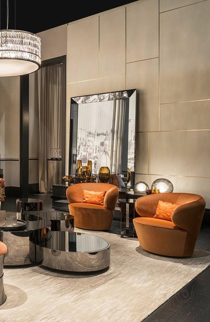 meubles art deco, fauteuils oranges, tables rondes basses, mur beige