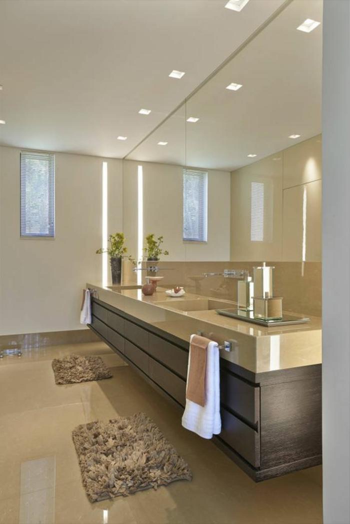 miroir lumineux salle de bain sur le mur entier avec un meuble suspendu sur toute la longueur