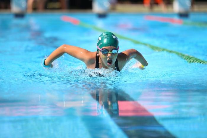 exercice pour maigrir, piscine intérieure, lunettes de natation rose, maillot de natation femme, bonnet de natation vert