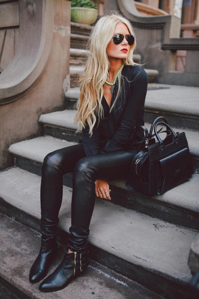 vetement noir, chemise noire avec décolleté en V, sac à main en cuir, cheveux blonds bouclés