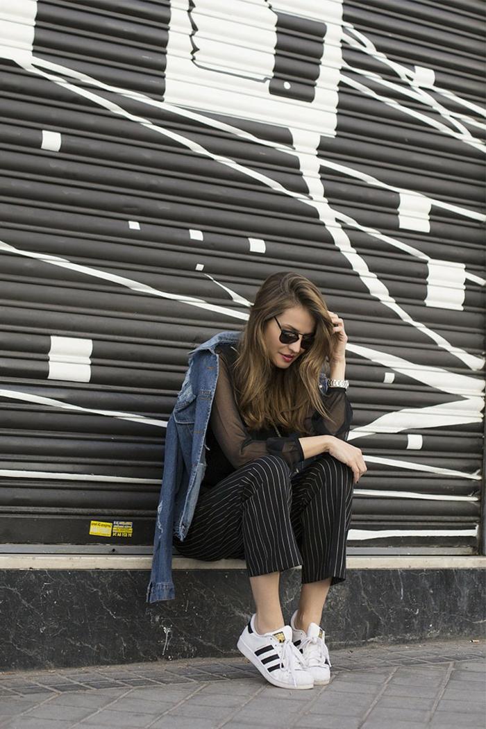vetement noir, lunettes de soleil noires, baskets blancs et noirs, veste en jeans, chemise noire
