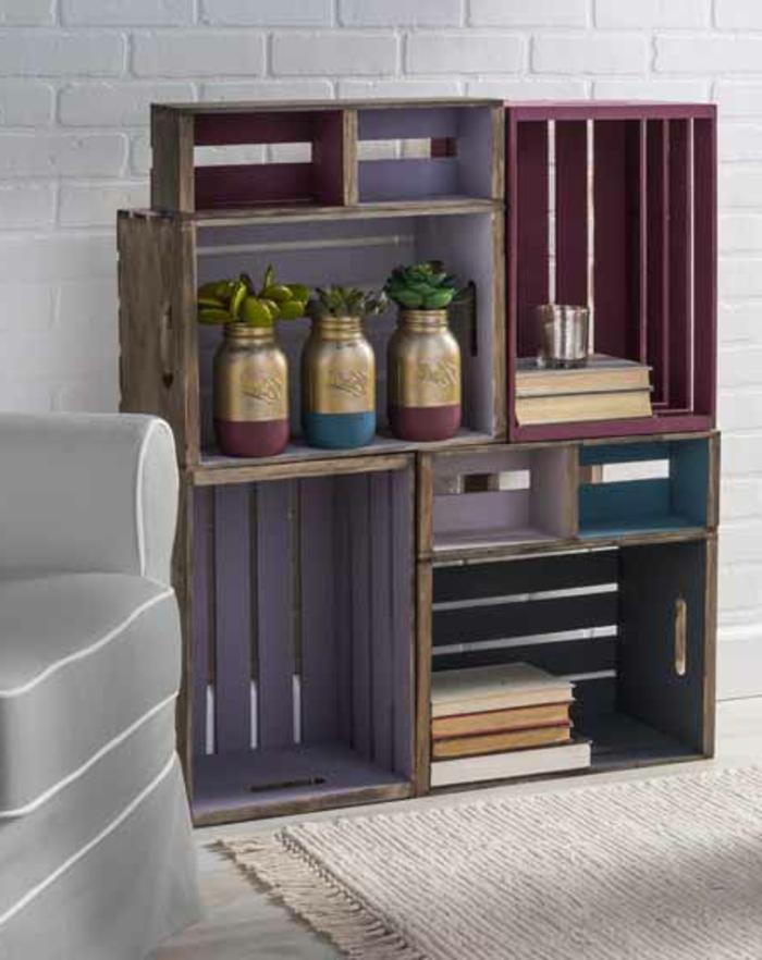 etagere cagette, plusieurs caisses repeintes, livres, bocaux en verre transformés en vases de fleurs, mur en briques blanches, fauteuil gris