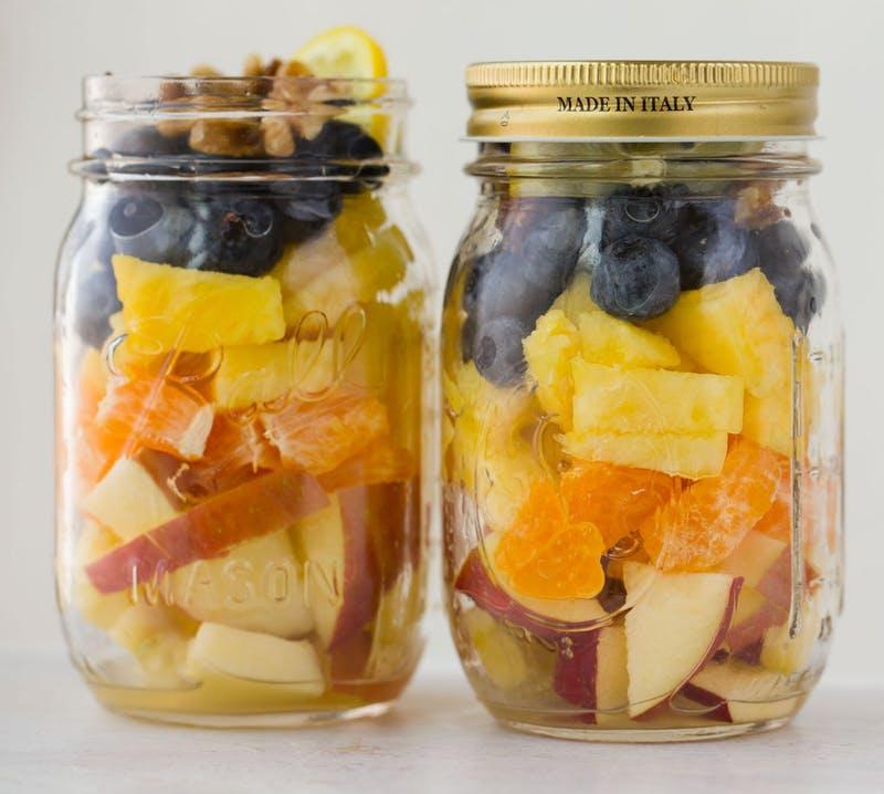 salade aux fruits dans un bocal en verre, idee picnic recette legère et facile à faire soi-mneme, ananas, pommes, tranches de mandarine et myrtilles, noix