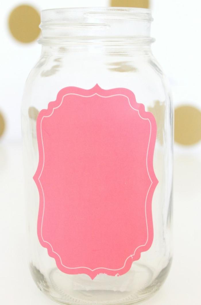 attacher l'étiquette au pot en verre avant de peindre, cadeau fête des mères à fabriquer, vase personnaliser, tutoriel facile premier étape