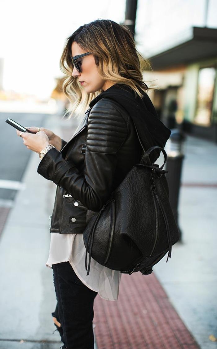 jean troué noir, chemise blanche longue, veste en cuir noir, sac à dos avec fermeture éclaire, cheveux balayage