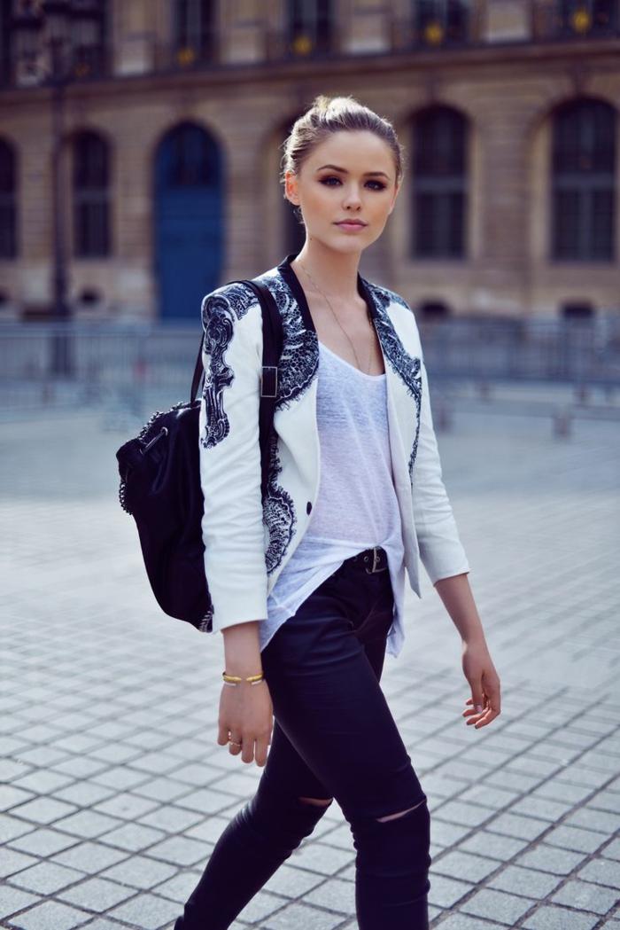 jean troué noir, bracelet en or, blazer blanc et noir, sac à dos en cuir, coiffure chignon blond