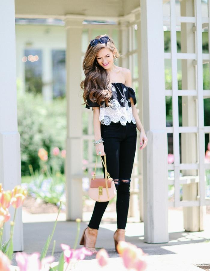 jean troué noir, sandales beige à talons, pochette en rose pastel, blouse blanche avec manches tombantes