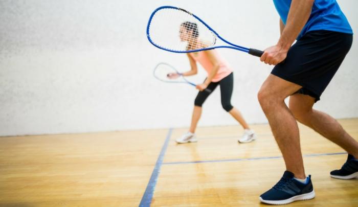 entrainement sportif, salle de squash, raquettes de squash bleus, shorts homme, baskets blancs femme