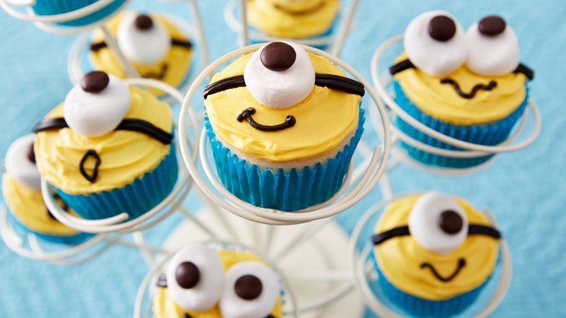 idée de cupcakes minions, glaçage jaune, guimauve en guise d oeil, décoration chocolat, caissette cupcake bleue