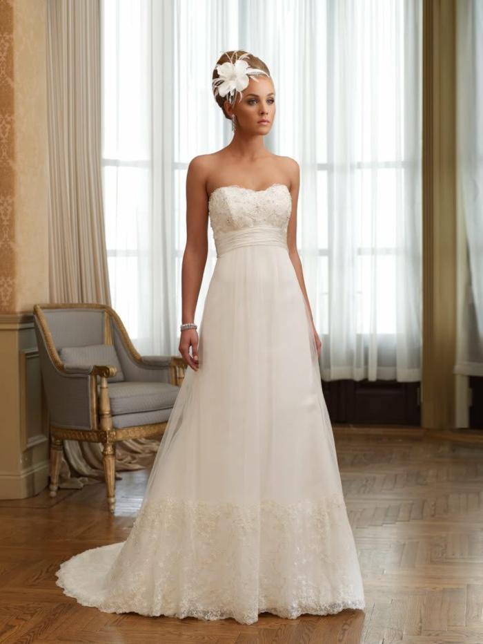 une élégante robe de mariée style empire sans bretelles avec accents en dentelle sur le bustier et le bas de la jupe