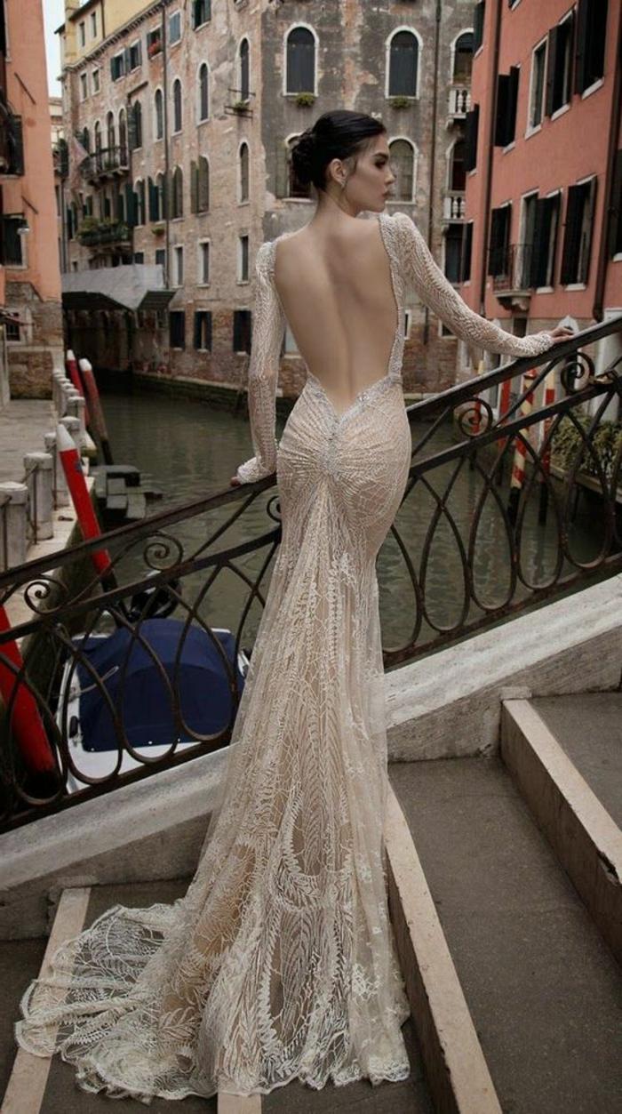 robe de mariée de couleur nude, manches longues, chignon, dos nu et traîne