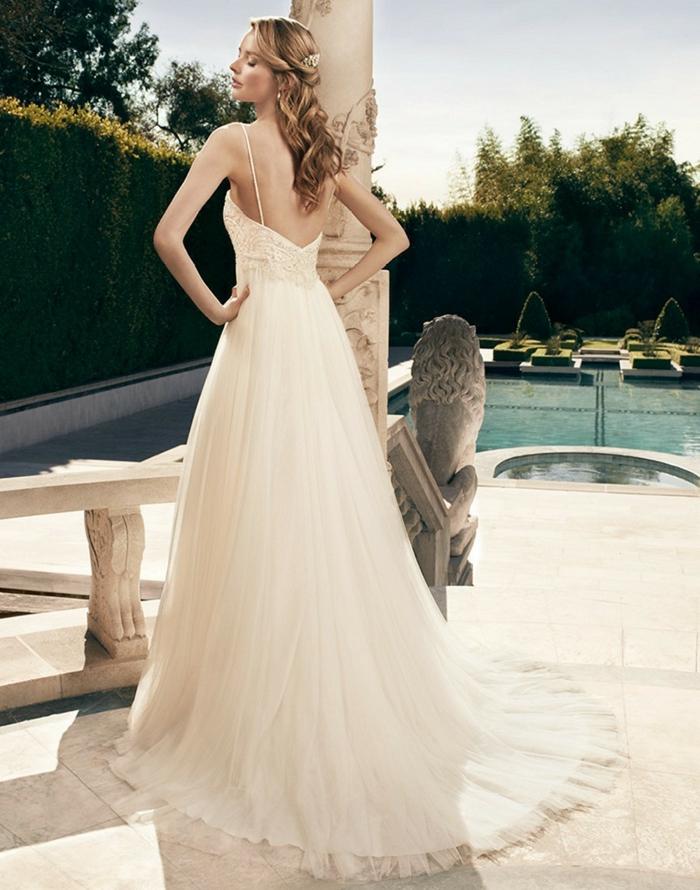 une robe empire longue à dos nus, une silhouette aérienne et légère, coiffure de mariée cheveux détachés ondulés