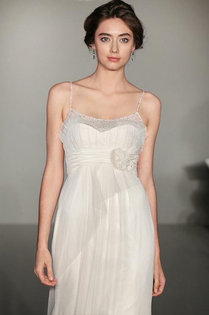 une robe de mariée style empire plissé à fines bretelles et bustier recouvert de tulle léger