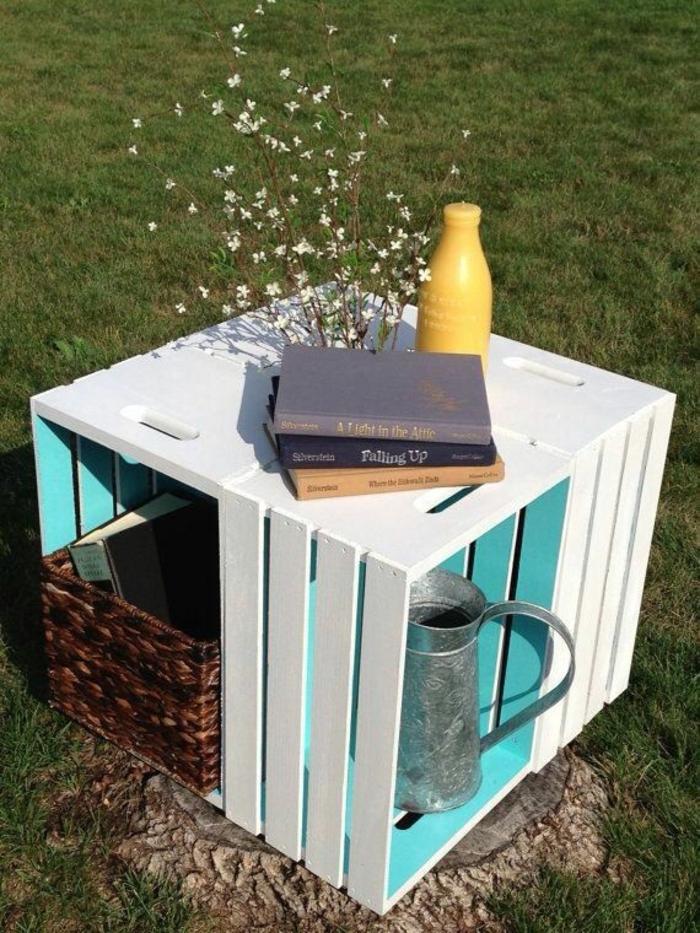 caisse en bois deco exterieur, petite table basse, couleur blanche, panier de rangement, livres, vase de fleurs, pelouse, projet diy cagette bois
