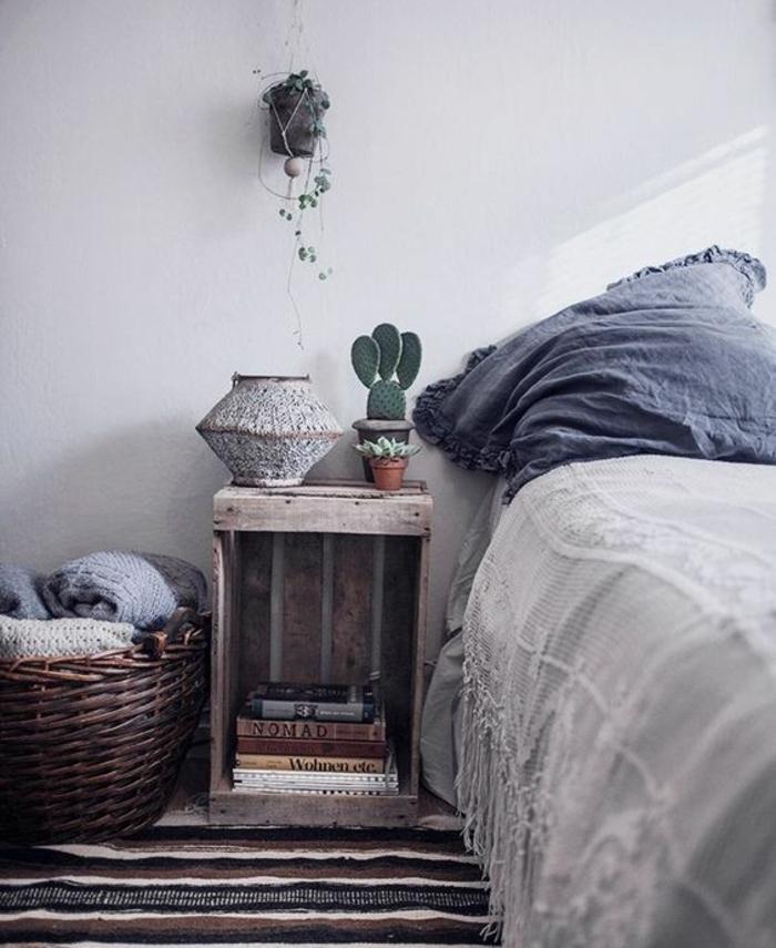 table de nuit en cagette vintage, livres, plantes, couverture de lit vintage, oreiller bleu, panier en rotin, tapis à rayures