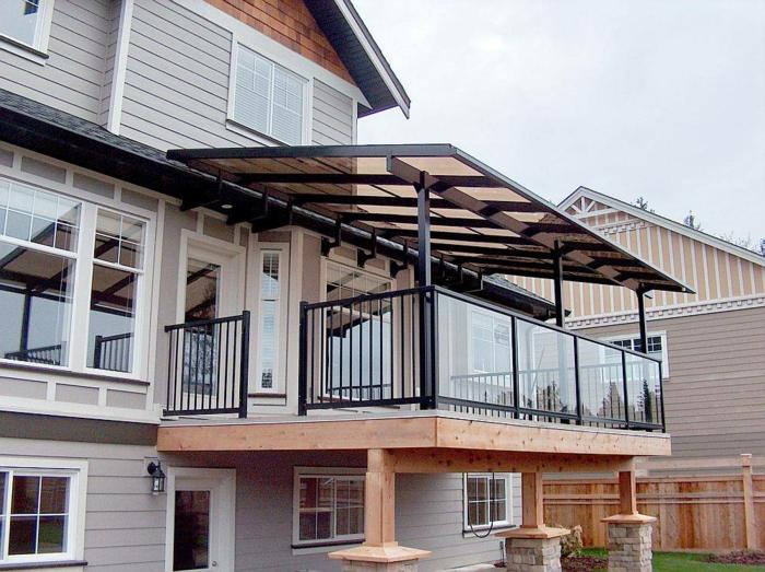 terrasse sur pilotis, rambarde en fer forgé, façade taupe poudré, colonne en pierre, grandes fenêtres