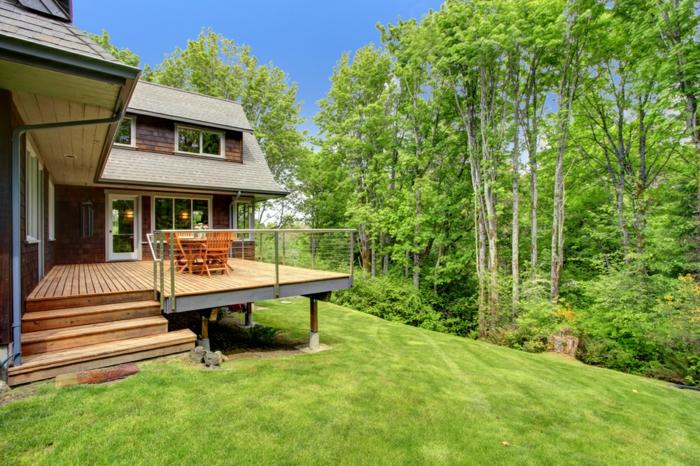 terrasse bois sur pilotis, marches en bois, façade en briques, petites fenêtres blanches, arbres