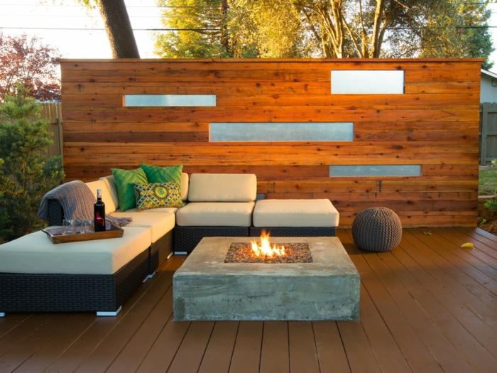 terrasse surélevée, plaid taupe poudré, canapé d'angle, murs en bois et verre, arbres, coussins décoratifs