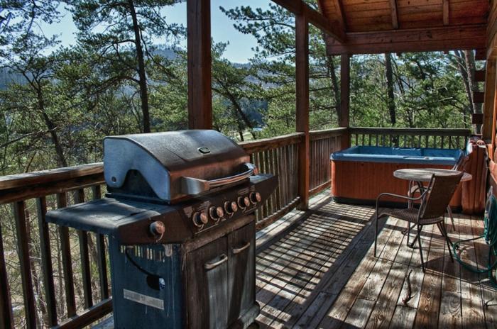 terrasse bois surélevée, chaise en fer forgé, auvent avec poutres en bois, jacuzzi, barbecue, table ronde
