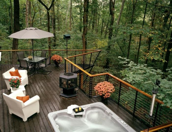 terrasse sur pilotis, jacuzzi gris, fleurs oranges, salon de jardin noir, parasol gris, fauteuil blanc, vue sur la forêt