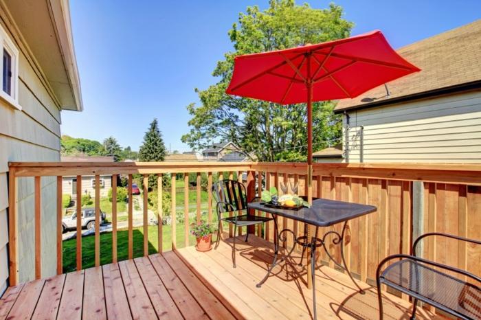 construire une terrasse, parasol rouge, table noire, chaises en fer forgé, rambarde en bois