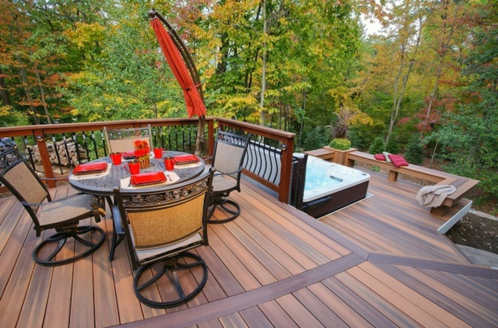 terrasse surélevée, jacuzzi, salon de jardin, table ronde, rambarde en bois, vue sur la forêt