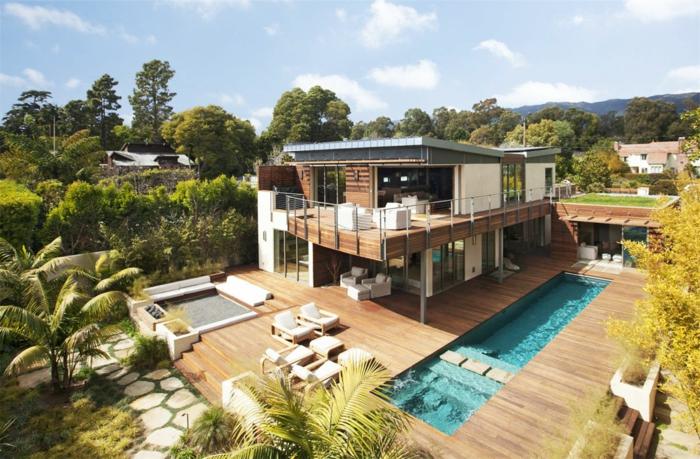 terrasse surélevée, façade en bois, piscine rectangulaire, transats blancs, salon de jardin blanc, arbres