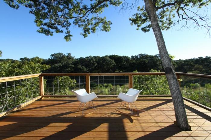 terrasse surélevée, chaises blanches, arbres, vue sur la forêt, rambarde en bois, arbres