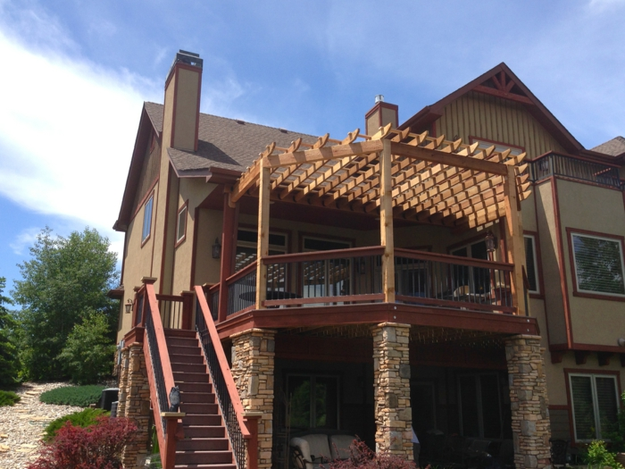 construire une terrasse, façade beige, fenêtres blanches, colonnes en pierre, canapé de jardin en blanc, auvent en bois