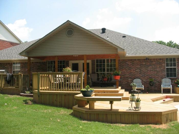 construire une terrasse, pot à fleur blanc, façade en briques, pot à fleur rouge, chaise en blanc et bleu, rampe en bois