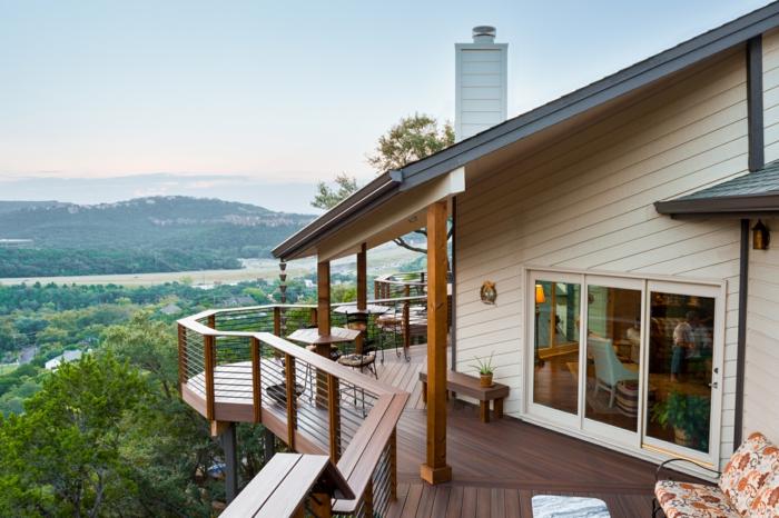 terrasse sur pilotis, vue d'en haut, façade beige, banc de jardin avec matelas multicolore, chaise en bois