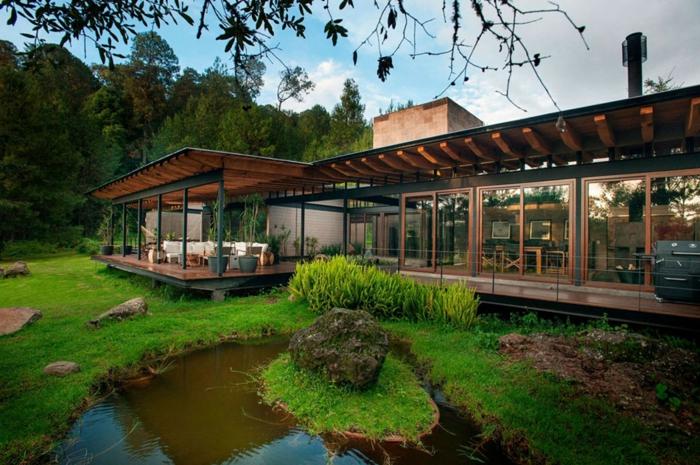 construire une terrasse, gazon vert, rocher, bassin d'eau, grandes fenêtres, auvents avec poutres en bois