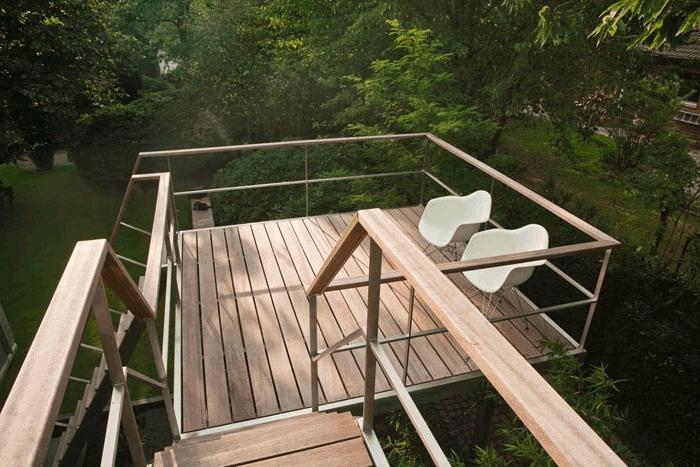 terrasse bois surélevée, chaises blanches, vue sur le jardin, rambarde en bois, escalier en bois