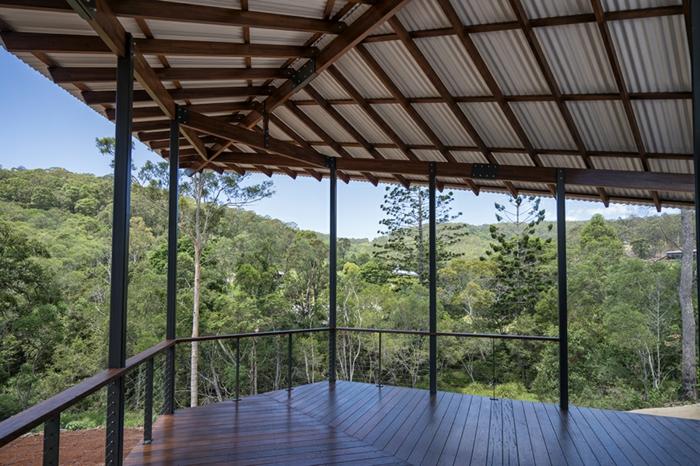 terrasse bois surélevée, auvent en bois, vue d'en haut, forêt, arbres, rampe en bois et fer forgé