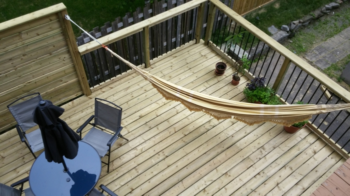 terrasse surélevée, table ronde noire, chaises noires, parasol noir, hamac beige, plantes vertes, jardin, clôture en bois