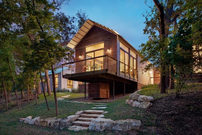 terrasse surélevée, maison en bois, grandes fenêtres, sentier en pierre, arbres, gazon vert